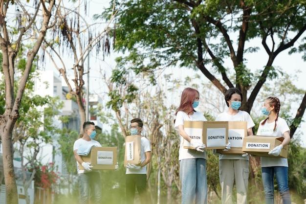 Gruppo di giovani volontari in maschere mediche che si radunano nel parco per raccogliere donazioni per fondazioni di beneficenza
