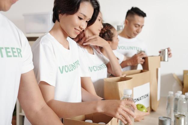 Gruppo di giovani volontari che imballano generi alimentari in pacchi di carta quando lavorano in un'organizzazione di beneficenza per la consegna delle spedizioni