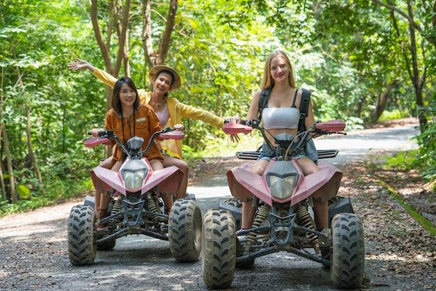 Gruppo giovane donna in sella a un'avventura di viaggio in auto fuoristrada o atv sulla montagna