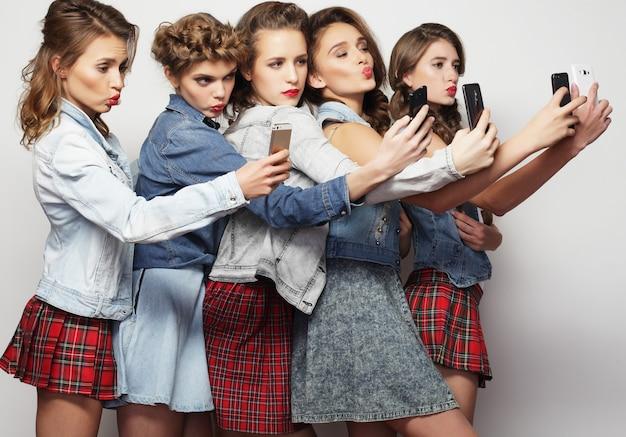 Gruppo di giovani donne che guardano i loro smartphone