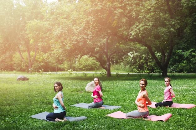 Un gruppo di giovani donne che fanno esercizi di yoga sotto l'effetto della luce solare dell'aria fresca