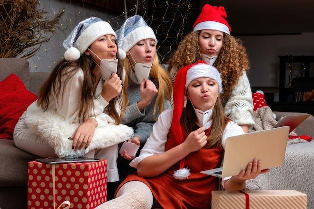Un gruppo di giovani donne che indossano cappelli natalizi e maschere protettive, risponde alle videochiamate durante il coronavirus, il coronavirus e il concetto di natale