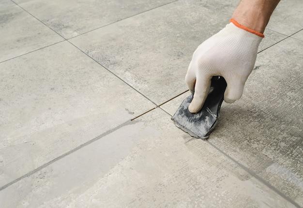Stuccatura di piastrelle in ceramica. piastrellisti che riempiono lo spazio tra le piastrelle usando una spatola di gomma.
