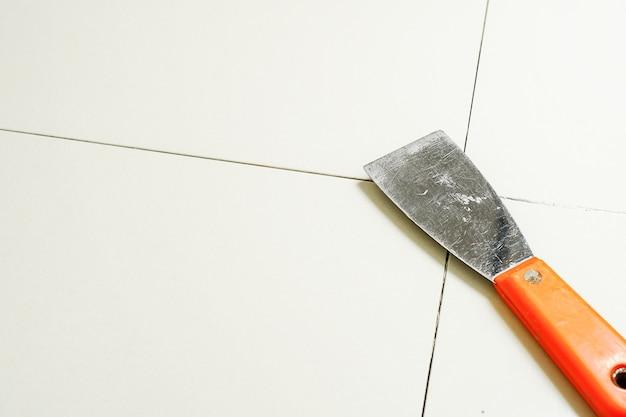 Stuccatura di piastrelle di ceramica piastrellisti che riempiono lo spazio tra le piastrelle utilizzando un acciaio inossidabile