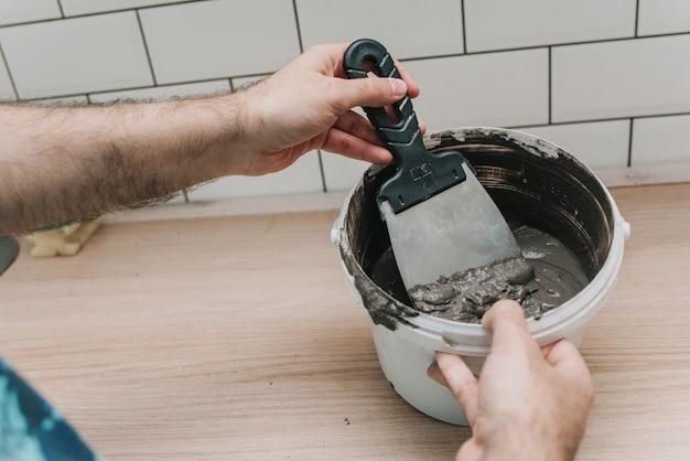 Stuccatura di piastrelle in cucina. riparazione. maialino di piastrelle