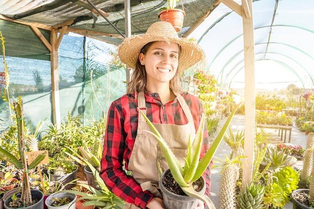 Coltivazione di piante di aloe in una serra. sorridente giovane donna professionale