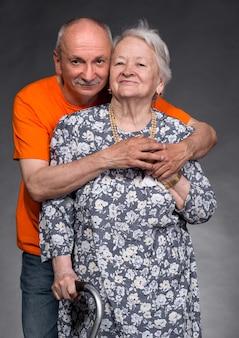 Un figlio adulto con la sua mamma anziana su un muro grigio