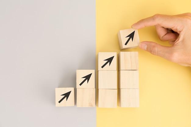 La crescita del concetto di business. mano che organizza il blocco di legno per la crescita del business e il processo per il successo