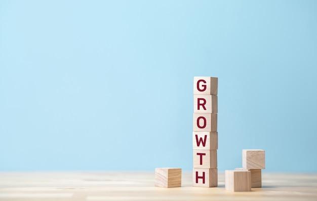 Concetti di crescita e successo con testo su blocco di legno