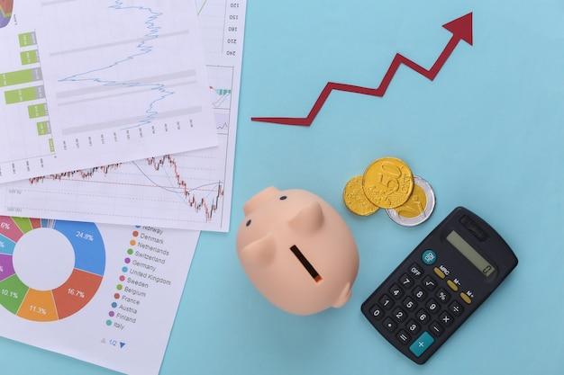 Freccia verso l'alto di crescita, grafici e tabelle, salvadanaio, monete e calcolatrice sull'azzurro. successo aziendale