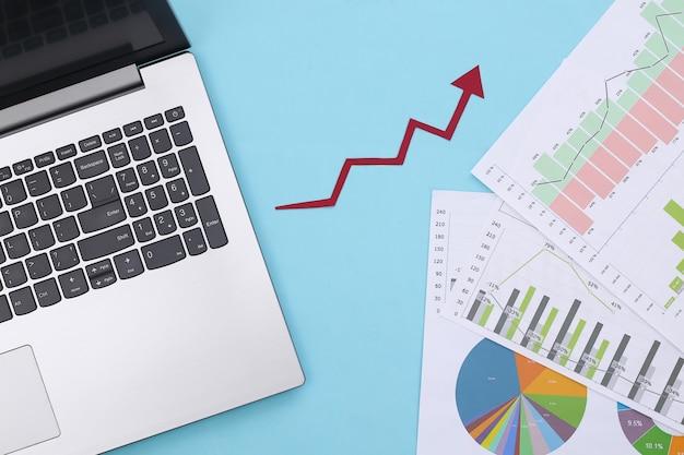 Freccia verso l'alto, grafici e grafici di crescita con il computer portatile su un blu