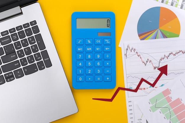 Freccia verso l'alto di crescita, grafici e grafici con laptop e calcolatrice su giallo. affari online. successo aziendale