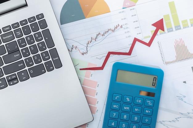 Freccia verso l'alto di crescita, grafici e grafici con laptop e calcolatrice