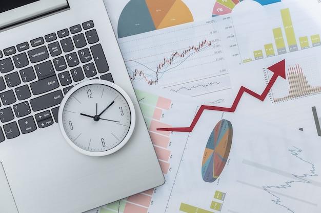Freccia di crescita verso l'alto, grafici e grafici con laptop e orologio