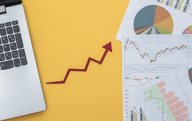 Freccia verso l'alto, grafici e grafici di crescita con il computer portatile su colore giallo. affari online. successo aziendale