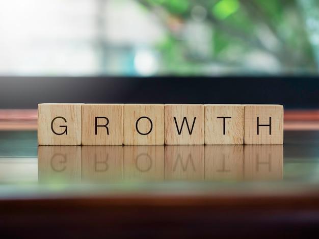 Crescita, parole sui blocchetti di legno del cubo sullo scrittorio di legno marrone e sul fondo verde della natura con lo spazio della copia. successo aziendale che cresce concetto.