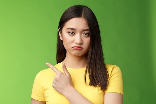 Scontrosa ragazza asiatica carina arrabbiata che si lamenta stanca, prosciugata durante gli esami universitari, indicando infelice, perdendo la concorrenza, indicando a sinistra, imbronciata scontenta, stando sullo sfondo verde riluttante.