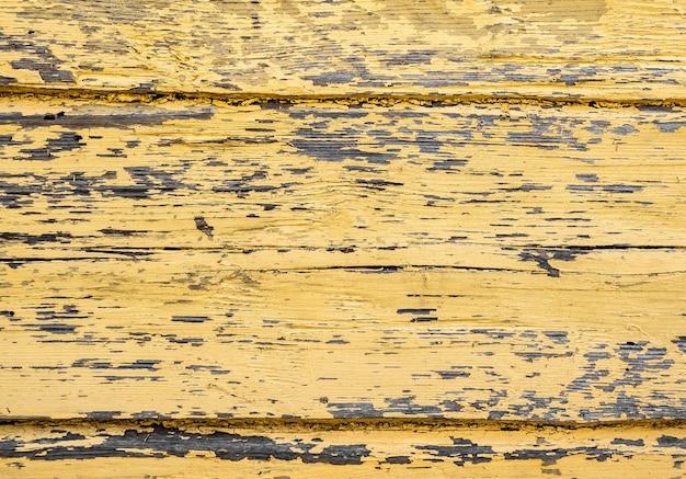 Priorità bassa di grunge dalla plancia di legno gialla stagionata. crepe nella vecchia vernice gialla.