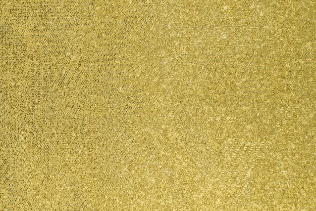 Priorità bassa di struttura della superficie dello stucco della parete dorata del grunge
