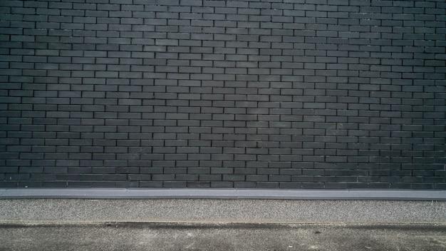 Sfondo sgangherato con muro di mattoni neri e terra di cemento. posto per il testo