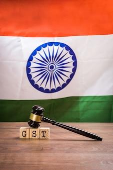 Gst basso in india - testo gst scritto su blocchi di legno con martelletto di legno sopra e bandiera nazionale indiana o tricolore sullo sfondo, messa a fuoco selettiva