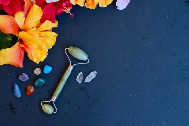 Gua sha, rullo di giada per massaggio facciale in pietra naturale con fiore naturale su sfondo posteriore