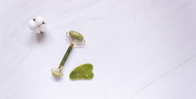 Rullo gua sha e raschietto per pietra di giada su sfondo bianco, spazio libero per il testo