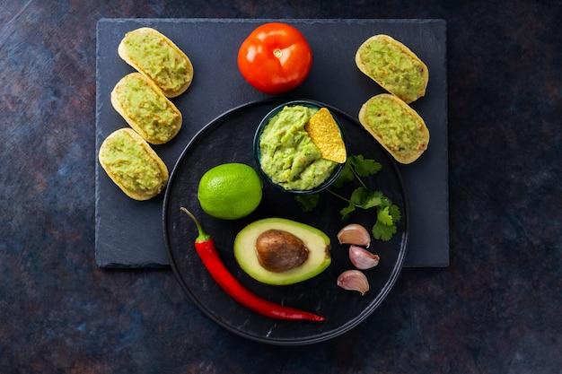 Salsa guacamole, chips di nachos e ingredienti su uno sfondo scuro. salsa guacamole messicana con avocado, ingredienti e nachos di mais. copia spazio. vista dall'alto