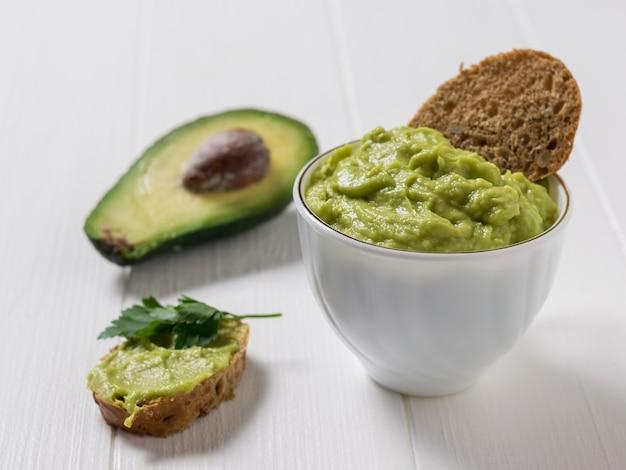 Guacamole in una tazza bianca con fette sottili di pane su un tavolo di legno bianco. dieta vegetariana cibo messicano avocado. cibo crudo.