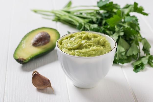 Guacamole in una tazza di porcellana bianca su un tavolo di legno. dieta vegetariana cibo messicano avocado. cibo crudo.
