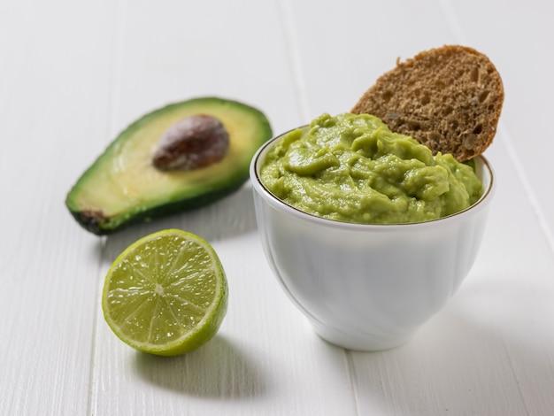 Guacamole con un pezzo di pane in una ciotola bianca, mezzo avocado e mezzo lime. dieta vegetariana cibo messicano avocado. cibo crudo.