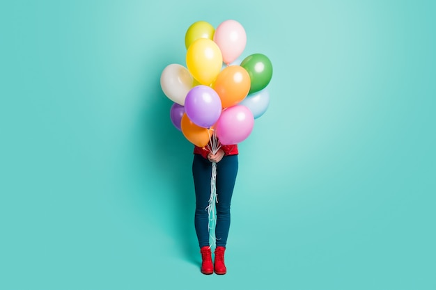 Indovina chi? foto a figura intera della signora nascosta che tiene molti palloni ad aria colorati che fanno visita a sorpresa indossare pantaloni cappotto rosso casual stivali isolati parete color verde acqua