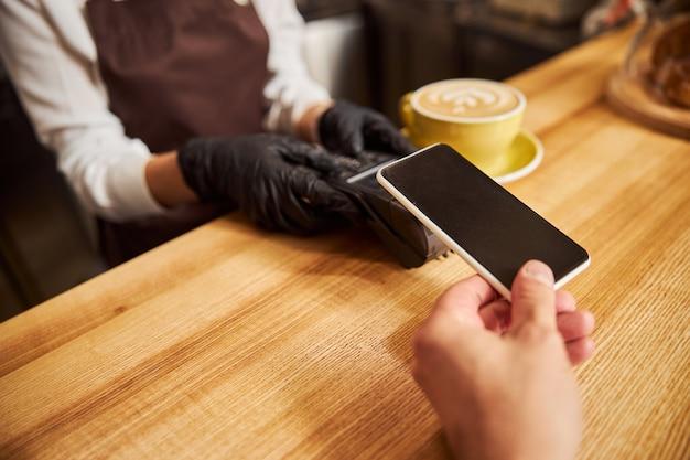 Ospite del bar che tiene lo smartphone vicino alla macchina di pagamento elettronico