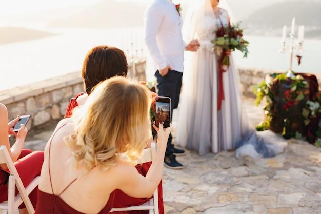 Ospiti alla cerimonia di matrimonio che hanno filmato la sposa e lo sposo sui telefoni