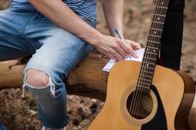 Concetto di idea dell'uomo della foresta della pubblicità della chitarra.