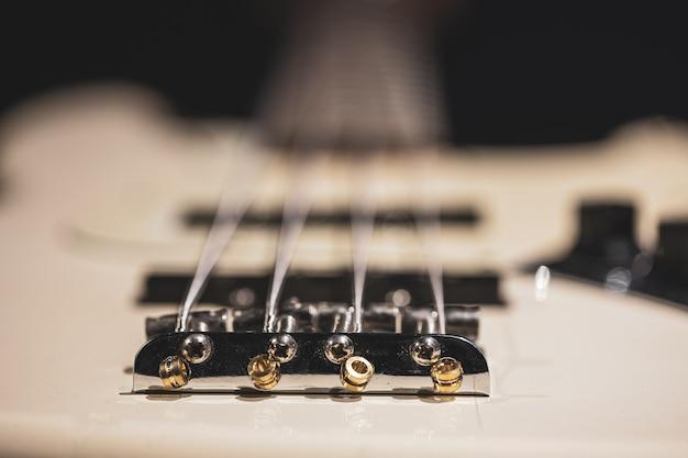 Dettagli delle corde della chitarra basso, primo piano delle corde di ferro su sfondo sfocato.