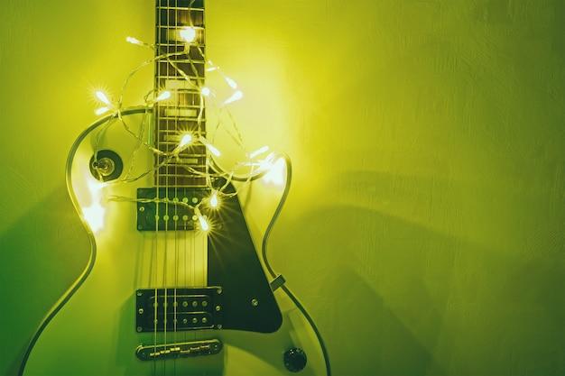 Chitarra su sfondo luminoso. regalo di capodanno sotto forma di costose chitarre elettriche. regalo per il musicista a natale. uno strumento musicale nei raggi delle luci splendenti.