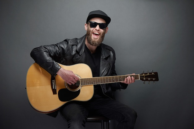 Chitarrista che canta in studio musicale. chitarrista hipster con barba e vestiti neri che suonano la chitarra acustica