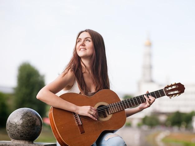 Concetto romantico del musicista della città della chitarra donna che suona uno strumento a corde. stile di vita delle persone di talento.