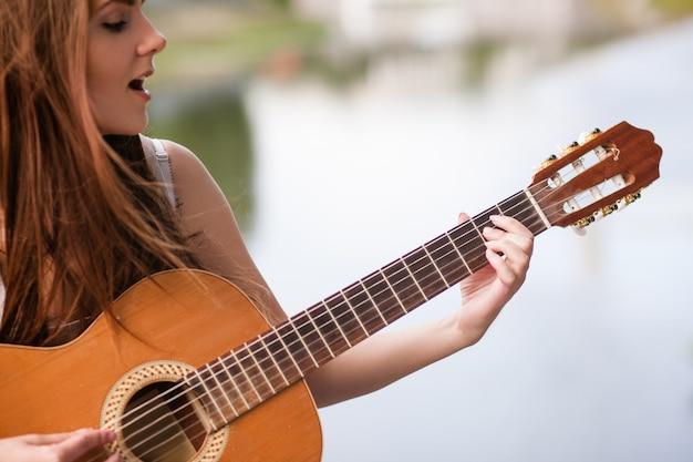 Esibizione del musicista della città romantica della chitarra donna che suona uno strumento a corde e canta. stile di vita delle persone di talento.