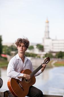 Concetto romantico del musicista della città dell'uomo della chitarra lezioni di suonare strumenti a corda. stile di vita delle persone di talento.