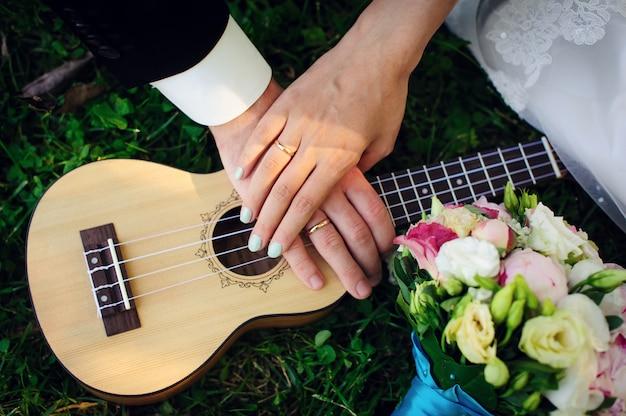 Chitarra, bouquet da sposa e mani degli sposi, primo piano. ukulele, mani della sposa e dello sposo con fedi nuziali sulle dita. romanticismo, amore, famiglia.