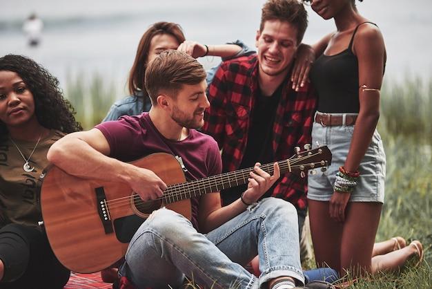 Chitarrista al centro dell'attenzione di tutti. un gruppo di persone fa un picnic sulla spiaggia. gli amici si divertono durante il fine settimana.