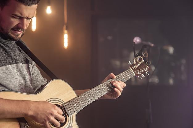 Chitarrista suonare la chitarra acustica contro sfocato sfondo scuro al concerto si chiuda.
