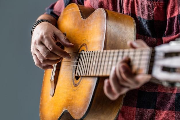 Chitarrista sul palco. chiuda sulla mano che suona la chitarra. chitarre acustiche. musicista maschio che suona la chitarra, strumento musicale. mani dell'uomo che suonano la chitarra acustica, primi piani. chitarre acustiche che suonano.
