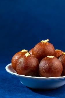 Gulab jamun, dessert indiano con frutta secca in ciotola bianca con tovagliolo