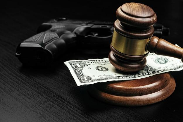 Pistola e martelletto del giudice sul tavolo