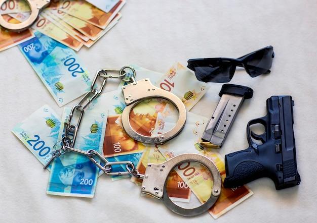La polizia armata ammanetta gli occhiali da sole sullo sfondo delle banconote del nuovo shekel israeliano