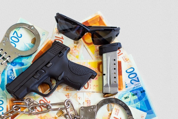 Pistola, due manette della polizia, occhiali da sole sullo sfondo delle banconote del nuovo shekel israeliano. pistola semiautomatica arma da fuoco con caricatore su shekel con le nuove banconote da 100, 200 nis, valuta. corruzione