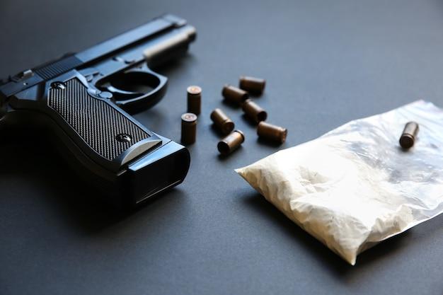 Pistola con proiettili sul tavolo. problemi criminali. farmaci nel pacchetto. vendita illegale.